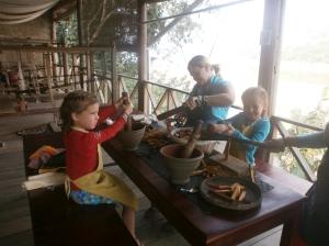 Maëlle écrase les graines d'annatto et Anaïk coupe le bois de sappan.