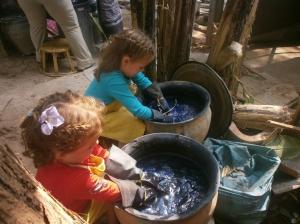 """Les filles pétrissent leur écharpe (Anaïk) et fil de soie (Maëlle) dans l'indigo fermenté """"qui pu super beaucoup""""."""