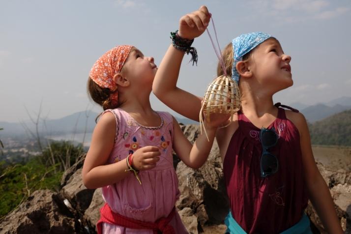 Les filles libèrent un oiseau comme offrande au temple du mont Phousi.